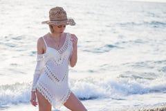 白色内衣和一个帽子的美丽的时髦的女人在海滩海洋 免版税库存图片