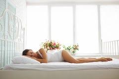 白色内衣的性感的亭亭玉立的妇女睡觉在与白色嘘床上的 库存照片