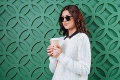 白色冬天拿着在绿色的毛线衣和黑太阳镜的时髦的妇女一次性咖啡杯, 图库摄影