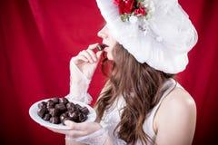 白色减速火箭帽子吃的美丽的小姐 免版税库存图片