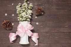 白色切削刀花在有丝带的花瓶在木背景和杉木锥体 库存照片