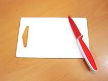 白色切板和红色刀子 库存图片