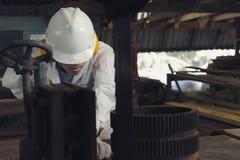 白色制服和切开一块木头在垂直的带的安全设备的专业年轻亚裔工作者看见了在鲤鱼的机器 免版税库存图片