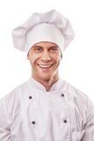 白色制服和帽子的站立的微笑的男性厨师 免版税图库摄影