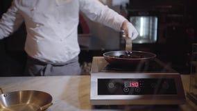 白色制服和橡胶手套倾吐的白酒的无法认出的厨师在煎锅,烹调在现代的淡菜 股票视频