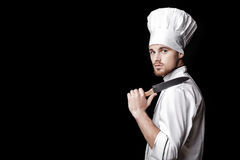 白色制服的年轻有胡子的人厨师拿着在黑背景的刀子 免版税库存照片