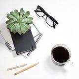 白色办公室桌面顶视图有植物、咖啡杯、玻璃和文具项目的 嘲笑 免版税图库摄影