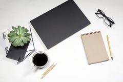 白色办公室桌面顶视图有膝上型计算机键盘、植物、咖啡杯、玻璃和文具项目的 嘲笑 免版税库存图片
