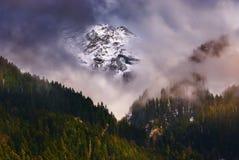 白色加盖的山穿甲通过云彩 库存图片