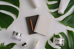 白色化妆产品和绿色叶子在颜色背景 免版税图库摄影