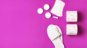 白色化妆拖鞋,卫生学项目,垫圈,棉塞,化装棉,在桃红色背景顶视图平的位置的手纸 化妆用品 库存照片