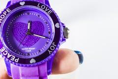 白色单音背景 在手上的紫罗兰色电子时钟 字 爱 题字的一空格 库存图片