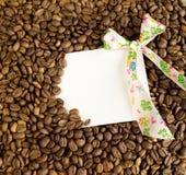 白色卡片和弓在咖啡豆背景  免版税库存照片