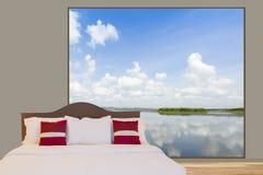 白色卧具板料和枕头在床上在一间屋子里有大窗口的把湖进行下去有多云蓝天视图作为背景 库存图片
