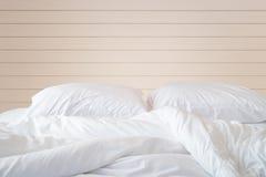 白色卧具板料和枕头在木墙壁室背景, 库存照片