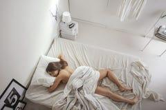 白色卧室。睡觉在床上的妇女。 免版税库存照片