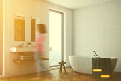 白色卫生间,白色木盆,角落,妇女 免版税库存图片