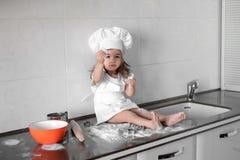 白色厨师帽子和围裙的小微笑的女婴面包师揉在tle厨房的面团 库存图片