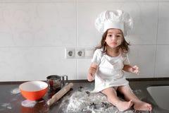 白色厨师帽子和围裙的小微笑的女婴面包师揉在tle厨房的面团 免版税库存图片