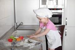 白色厨师帽子和围裙的小微笑的女婴面包师揉在tle厨房的面团 库存照片
