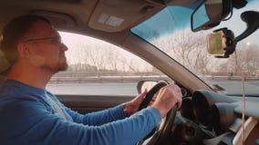 白色司机在有背后照明的汽车 在太阳的司机半眯着的眼睛 智能手机在电话持有人在后面看法镜子下 影视素材