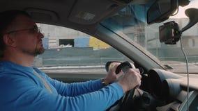 白色司机驾驶通过城市和中止的建筑的汽车 日落在城市 影视素材