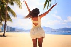 白色后侧方视图的亭亭玉立的女孩摆在用手在海滩 库存照片