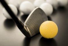 白色和一黄色高尔夫球在黑地板上 的个性 库存图片