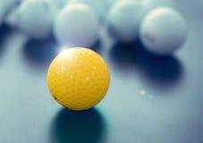 白色和一黄色高尔夫球在黑地板上 的个性 图库摄影