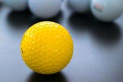 白色和一黄色高尔夫球在黑地板上 的个性 免版税库存图片