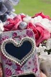 白色和桃红色人为玫瑰和一个手机花束有心脏标志的 库存图片