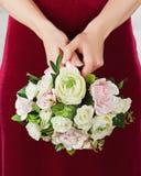 从白色和桃红色玫瑰的婚礼花束在新娘的手上 免版税图库摄影