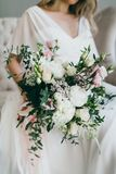 白色和桃红色花华美的花束在迷人的新娘的手上一件白色礼服的 附庸风雅 库存照片