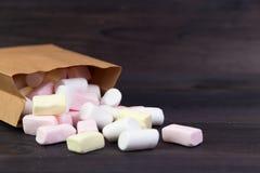 白色和桃红色蛋白软糖溢出在包裹外面 免版税库存照片