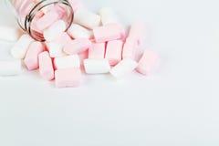 白色和桃红色蛋白软糖溢出在玻璃外面 免版税库存图片