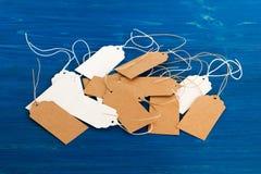 白色和棕色白纸价牌或标号组在蓝色木背景 库存图片