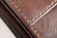 白色和棕色螺纹缝黑色和褐色的宏观细节缝了皮革钱包 库存照片