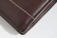 白色和棕色螺纹缝黑色和褐色的宏观细节缝了皮革钱包 免版税库存照片