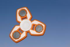 白色和橙色坐立不安锭床工人应力消除玩具在天空后面 免版税库存图片