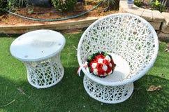 白色和猩红色玫瑰婚礼花束在一把柳条白色圆的椅子的 库存照片