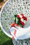 白色和猩红色玫瑰婚礼花束在一把柳条白色圆的椅子的 库存图片