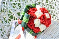 白色和猩红色玫瑰婚礼花束在一把柳条白色椅子的 免版税库存照片