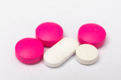 白色和玫瑰圆的药片和卵形坚硬胶囊 免版税图库摄影