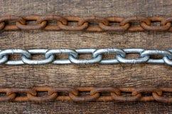 白色和生锈的铁链子行在木纹理背景的 库存照片