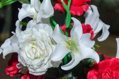 白色和红色人造花百合和玫瑰在黑背景 免版税库存图片