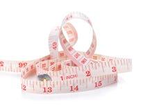 白色和红色测量的磁带在白色背景,厘米 免版税库存图片