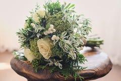 白色和绿色花架新娘花束在椅子的反对一种轻的织品 免版税库存照片