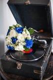白色和蓝色玫瑰新娘` s花束在一个老转盘的音乐板材 库存照片