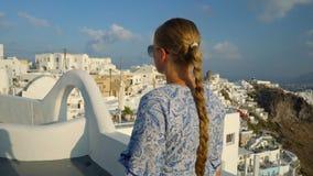 白色和蓝色礼服的愉快的妇女享受她的在圣托里尼,希腊的假日 在破火山口和爱琴海的看法从 股票视频