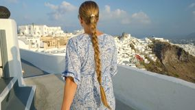 白色和蓝色礼服的愉快的妇女享受她的在圣托里尼,希腊的假日 在破火山口和爱琴海的看法从 影视素材